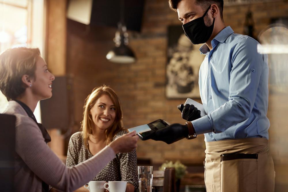 Waiter taking payment in restaurant