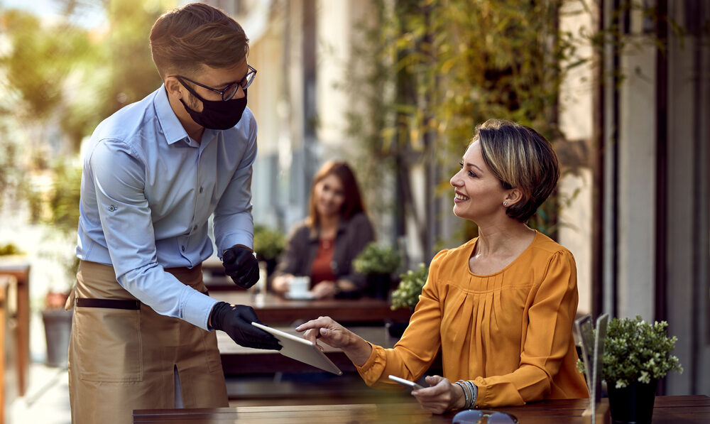 Waiter serving woman outdoors with mask