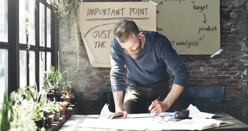 Business man making notes at desk